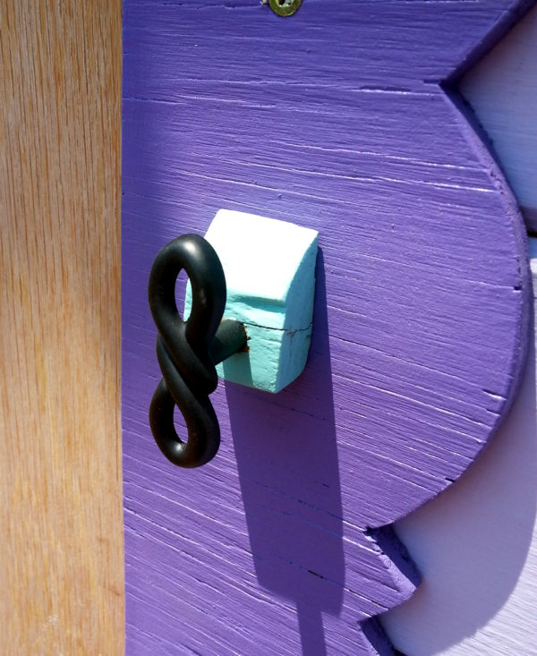 A black drawer pull, shaped like an infinity symbol with an extra twist in the middle, is fastened to a small squarish block of wood, which is in turn fastened to the purple trim next to Tyrava's front door.