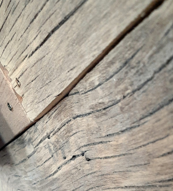 A closeup of where three boards come together on the back wall. All three are sanded smooth, to a pale grey, with shallow cracks following the grain of the wood.