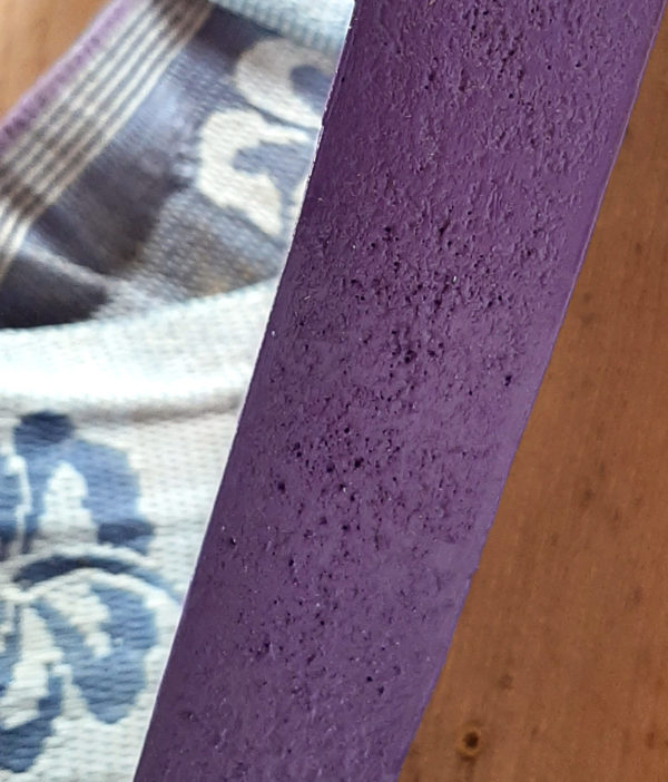 A close view of the edge of the front door -- it's painted a dark purple, but it's a rough surface, & the paint doesn't quite fill all the tiny holes & gaps.