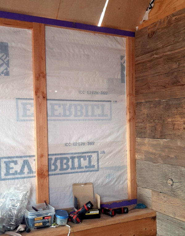 This section of the side wall is framed by two upright 2x4s, set three feet apart. Between them is currently just white Tyvek housewrap.
