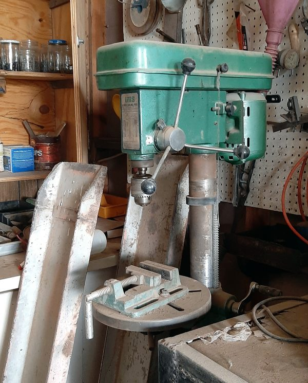 An old-style drill press sits in the corner of what's obviously a workshop. It's all metal, none of this modern plastic stuff. The top part is painted teal & there's a LOT of dust on it.