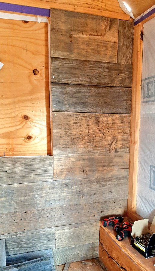 Part of an interior wall, between a corner & a boarded-up window. This entire wall section, about two feet wide, is finished, with reclaimed wood in widths from six inches to almost a foot.