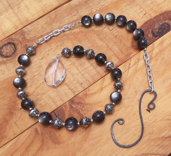 The crystal's now the end of a dangling suncatcher which also has short lengths of silver-coloured chain & alternating black & silver-coloured beads.