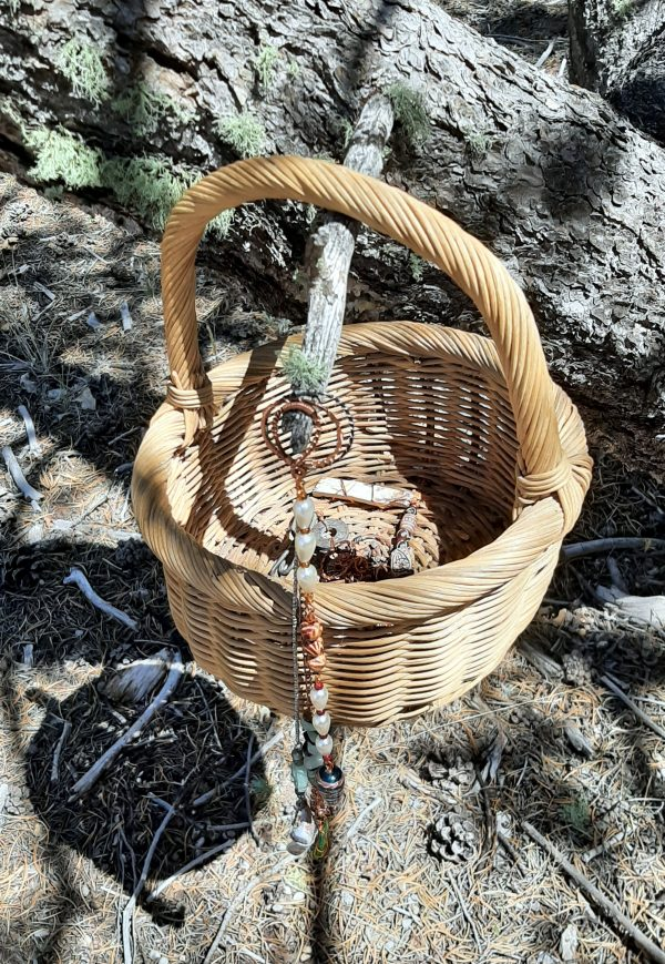 A basket hangs from a short stubby branch protruding from a treetrunk. A few beads ^& such are visible inside, & a couple of pendants dangle from the end of the broken branch.