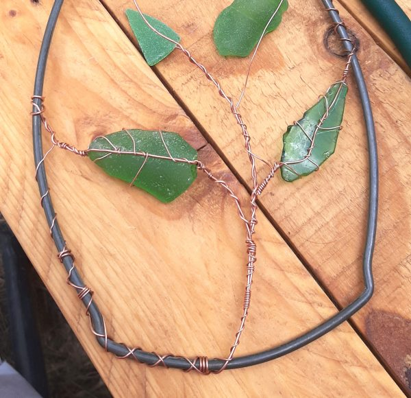 Both sea glass leaves are attached to the vine, branching out to either side of it.
