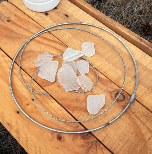 On a wooden table: a round steel hoop, perhaps a foot in diameter; about two feet of thick silvery wire composed of multiple thin wires plied together; & a pile of seaglass pieces ranging from about an inch to perhaps two inches in diameter.