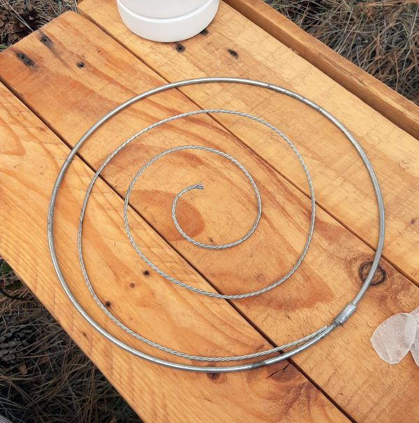 The wire's now in a neat spiral; the outer end is fastened to the hoop by more silvery-coloured wire.