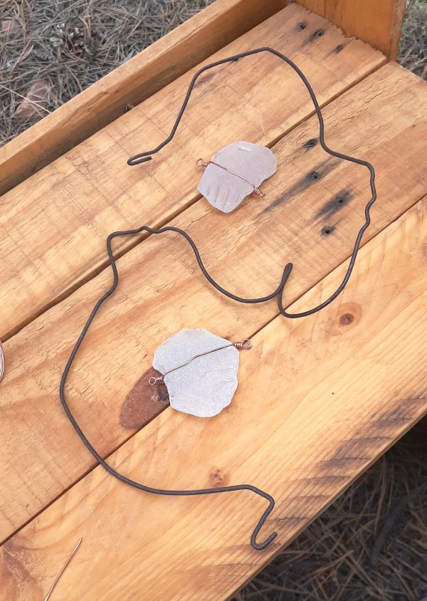 On a wood table: a weird bent piece of coathanger, shaped roughtly like a backwards S, but with lots of kinks & bends. Inside are two pieces of white seaglass, each roughly an inch and a half in diameter.