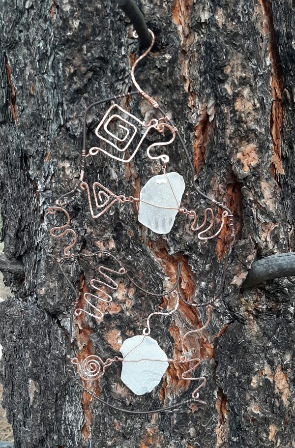 I hung the piece on a ponderosa tree to get a picture. The dark clothes hanger wire is nearly the same colour as the tree bark. The seaglass & the copper show up pretty well, though.