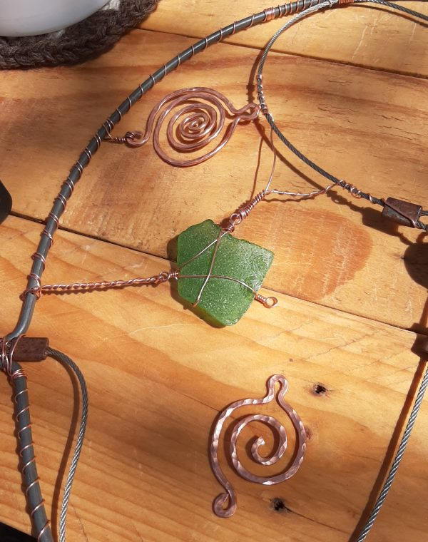 One of the pieces of seaglass is wrapped in copper wire. More wire connects it to one of the cables, to the metal circle, & to a small spiral of copper, hammered flat.