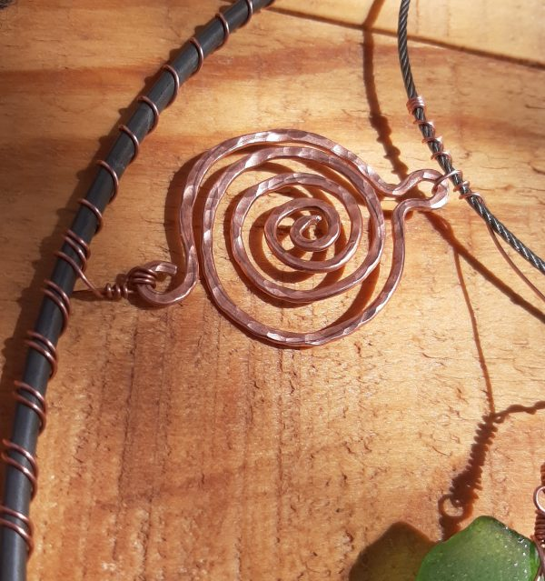 A closer view of the small spiral. It's maybe an inch and a half across, hammered flat & then textured by me hitting it with the round end of the hammer. It's got small loops at either end, & it's connected to the circle & to one of the cables by much thinner copper wire.