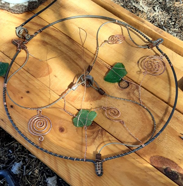 Two of the three sections of the piece are done. Each holds one piece of green seaglass & two copper spirals, hammered flat. They're connected to each other, & to the frame, with thinner copper wire.